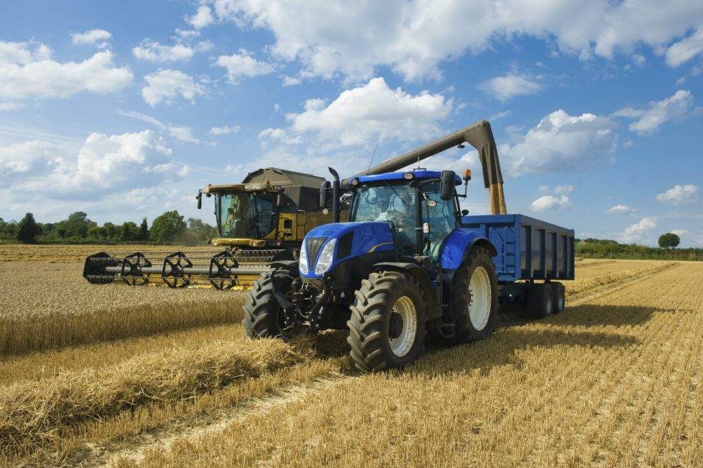 Combine harvester delivering harvested grain onto a grain trailer on a farm.