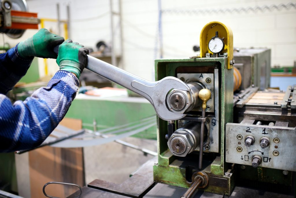 Worker adjusting machinery with large wrench