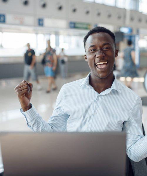 Businessman sitting at laptop in car dealership